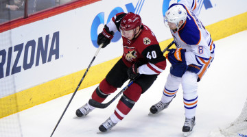 Mar 22, 2016; Glendale, AZ, USA; Arizona Coyotes left wing Alex Tanguay (40) carries the puck as Edmonton Oilers defenseman Griffin Reinhart (8) defends during the second period at Gila River Arena. Mandatory Credit: Matt Kartozian-USA TODAY Sports