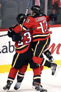 Dec 4, 2015; Calgary, Alberta, CAN; Calgary Flames left wing Johnny Gaudreau (13) jumps on center Jiri Hudler (24) and center Sean Monahan (23) to celebrate Hudler's  goal to tie the game in the third period with  against the Boston Bruins at Scotiabank Saddledome. Flames won 5-4 in overtime. Mandatory Credit: Candice Ward-USA TODAY Sports